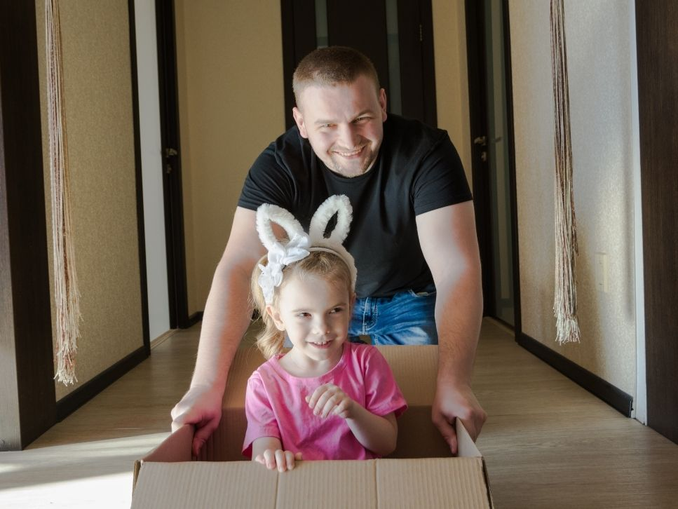 A family relocating man pushing daughter in box
